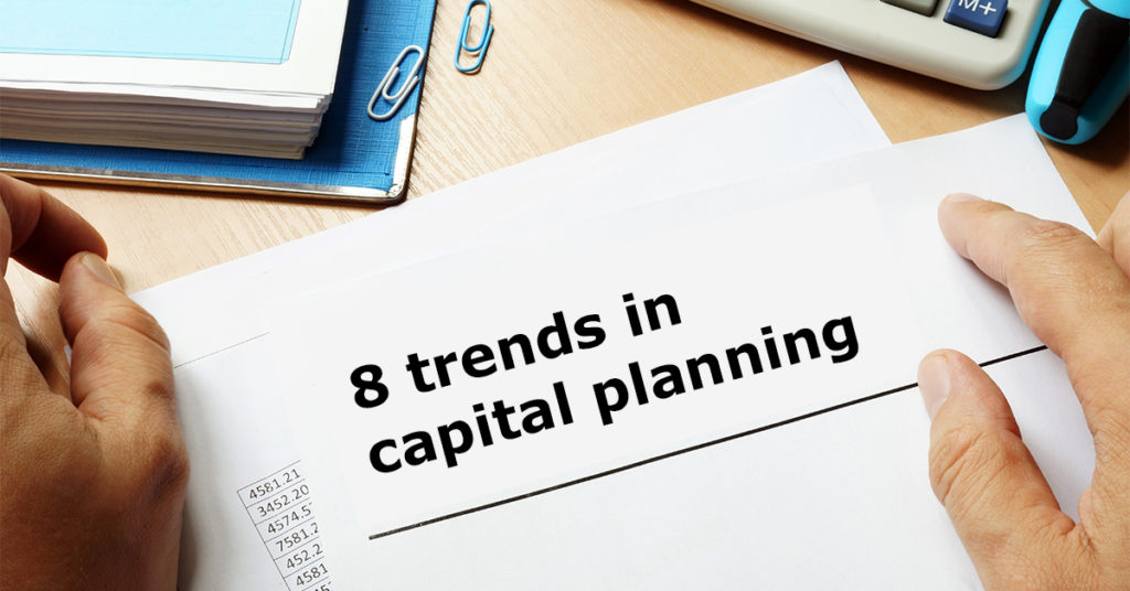 a man holding a piece of paper that says 8 trends in capital planning